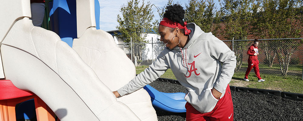 Basketball player doing community service at elementary school playground